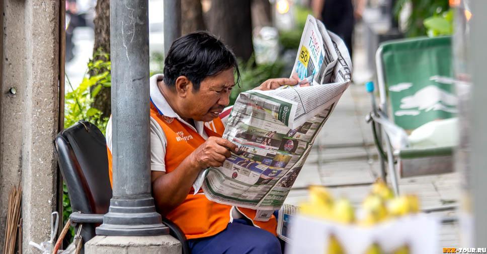 Таксист - мотобайщик читает газету в Бангкоке