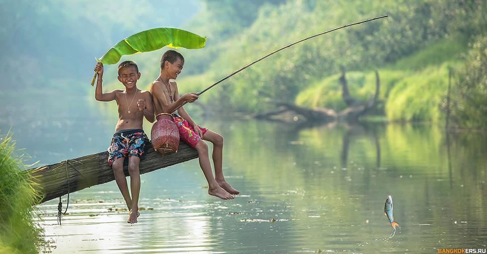 Дети ловят рыбу на реке, прикрываясь листом бамбука